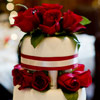 Romantic four-tiered cake with red ribbon and roses