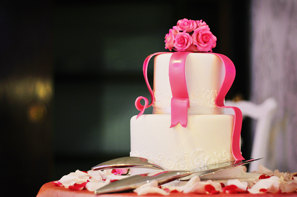Elegant two-tiered cake with pink ribbon and flower detailing