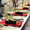 Modern red, black and white place settings at a long rectangle guest table with floral centerpieces