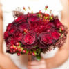 Winter-themed nosegay bouquet with dark red roses and berries