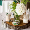 Clear Mason jar filled with white flowers and foliage atop a tree trunk disc