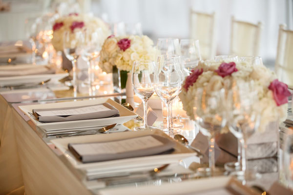 Floral centrepieces of white and pinks flowers with candles on mirrored table runner