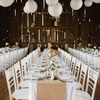 Elegant long tables with flag table numbers under a ceiling with paper lanterns