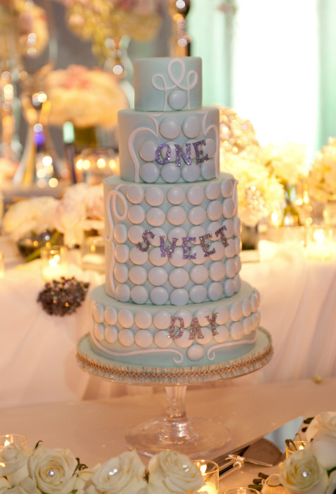 Whimsical four tiered mint green cake with white fondant accents and glitter text