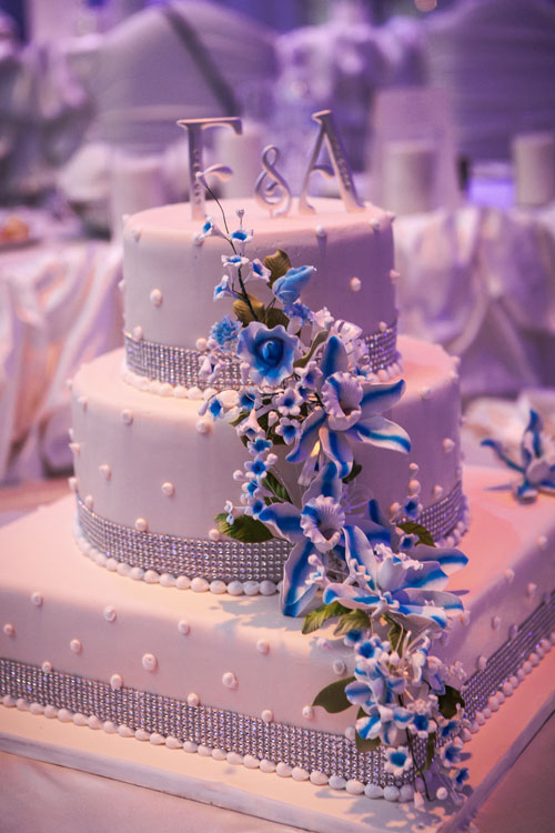 3 tier white cake with pearl detailing, diamond-style ribbons and cascading white & blue sugar flowers
