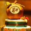 Harvest-themed two-tiered cake with ornate leaf detailing and apple topper