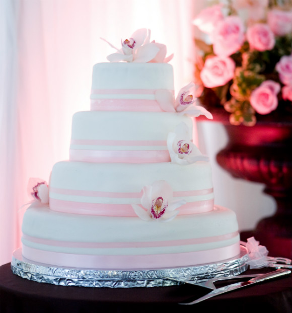 Five tier white fondant cake with pink fondant ribbon trim & orchid topper