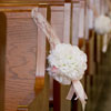 White flower bouquets tied with soft pink lace hanging off of church pews
