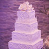 Four tier cake with rustic icing and edible white rose cake topper