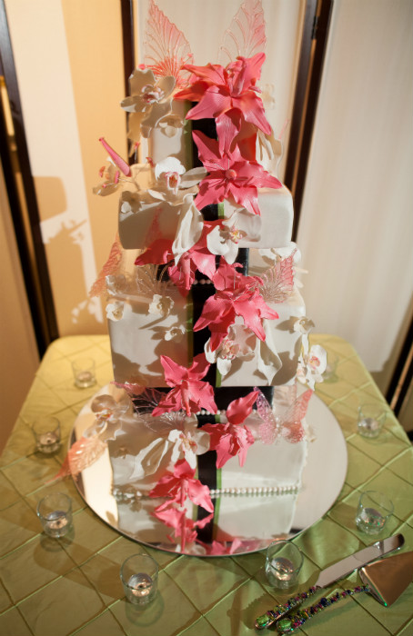 White four tier square cake with black and green ribbon fondant, piped pearl beading and white and coral floral accents