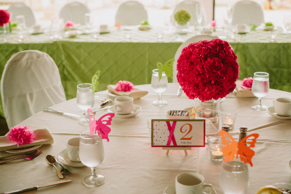 Simple table decor with white and lime green linens and fuchsia flower centre pieces.