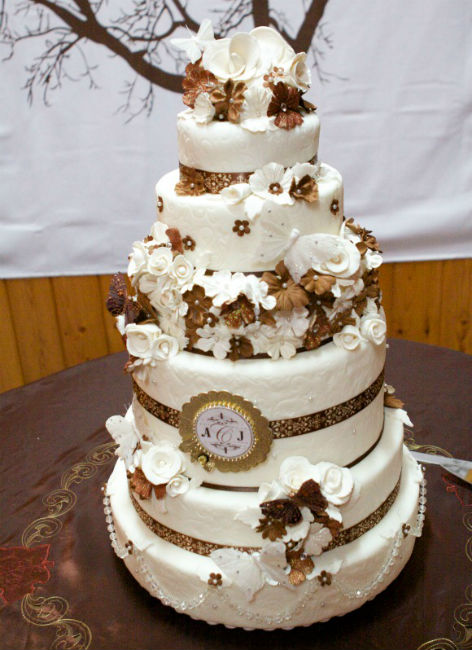 Four-tiered bronze-and-white cake with whimsical flower detailing