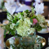 Small square vases filled with flowers on top of mirrors with surrounding candles