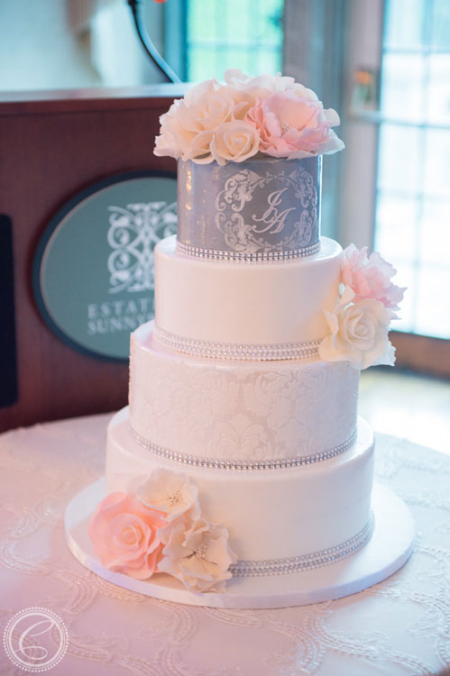 Four tier cake with crystal ribbon, unique stencilling and pink flowers