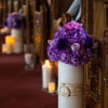 White marble vases with purple floral bouquets surrounded by candlelight along the aisle