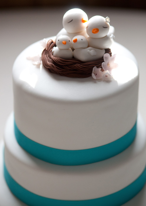 Modern white, two tier cake with teal trim and doves in nest topper