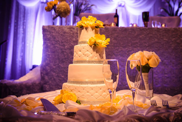 4 tier with diamond fondant pattern along with rhinestone ribbon and yellow florals