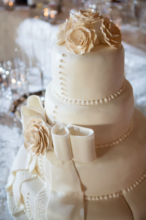Traditional four tier cream cake with embellished bow, pearl bead trim and peach roses