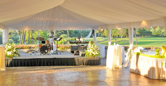 Tented Outdoor Dance Floor With Green And White Flowers