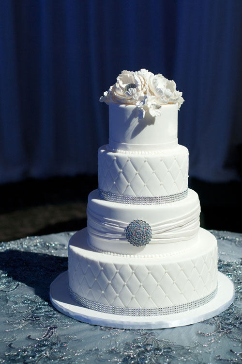 4 tier white-on-white detailed cake with studded broach and sugar flowers on top