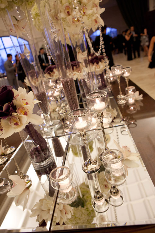 A stunning reception entrance table with crystals, vases, candles and flowers