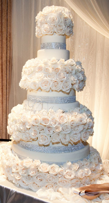 Four tier white cake with crystal trim and blush roses