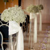 Tall glass vases adorned with baby's breath bouquets, tied with white lace ribbon amidst white & lavender rose petals