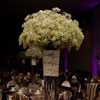 Floral centrepiece with baby's breath and purple flowers, surrounded by candlelight