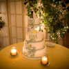 4 tier yellow and grey cake with yellow mini roses encased in glass underneath top tier
