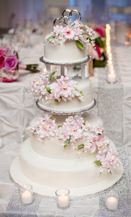 White four tier cake with piped accents and pink and white floral accents