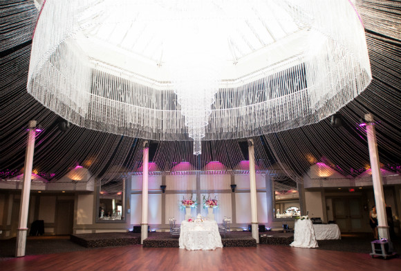 Stunning crystal chandelier and crystal ceiling accents highlight a head table for two