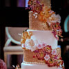 6 tier cake with gold encrusted layers and cascading florals