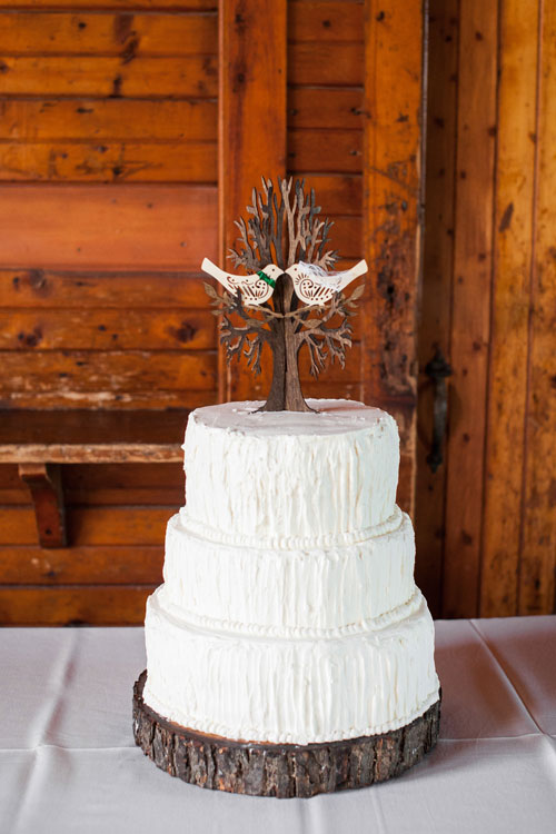 3 tier white cake with rustic detailing and love birds cake topper