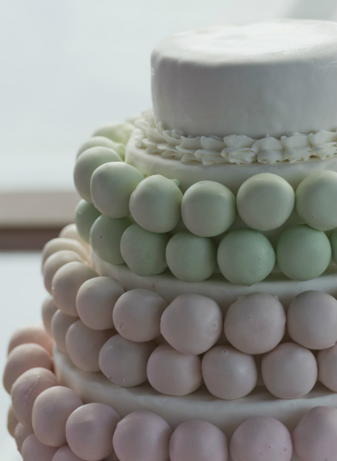 Four tier white cake with green and pink pastel accents