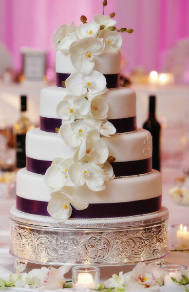 Modern four tier cake with cascading orchids and purple ribbon trim