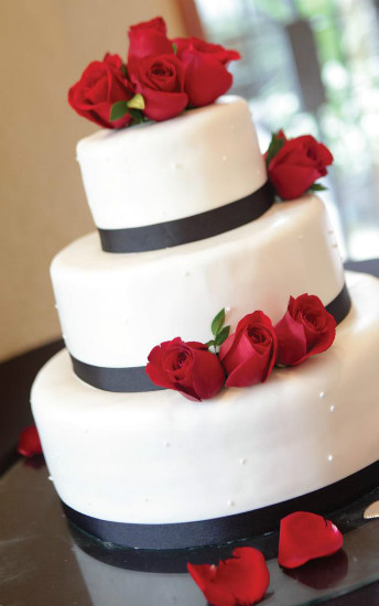 Modern elegant white cake with black ribbon trim and red fondant roses