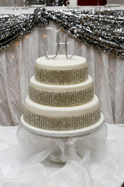 Three tier white fondant cake with rhinestone ribbon trim and silver monogram initial topper.