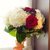 Colourful nosegay bouquet with red roses and white carnations
