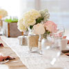 Mason jars filled with pink & white flowers on top of rustic table runners