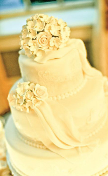 Elegant three tier cake with white rose bouquet topper and white pearl icing trim