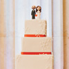 Four tier square cake with snowflake details, orange ribbon and adorable bride & groom cake topper