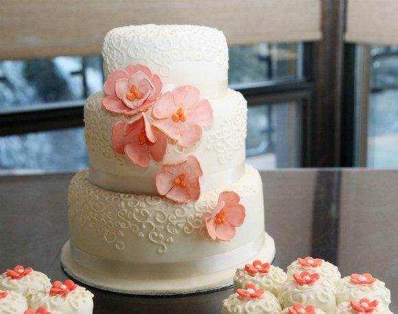 While three tier cake with champagne ribbon trim, peach floral accents and coordinated cupcakes