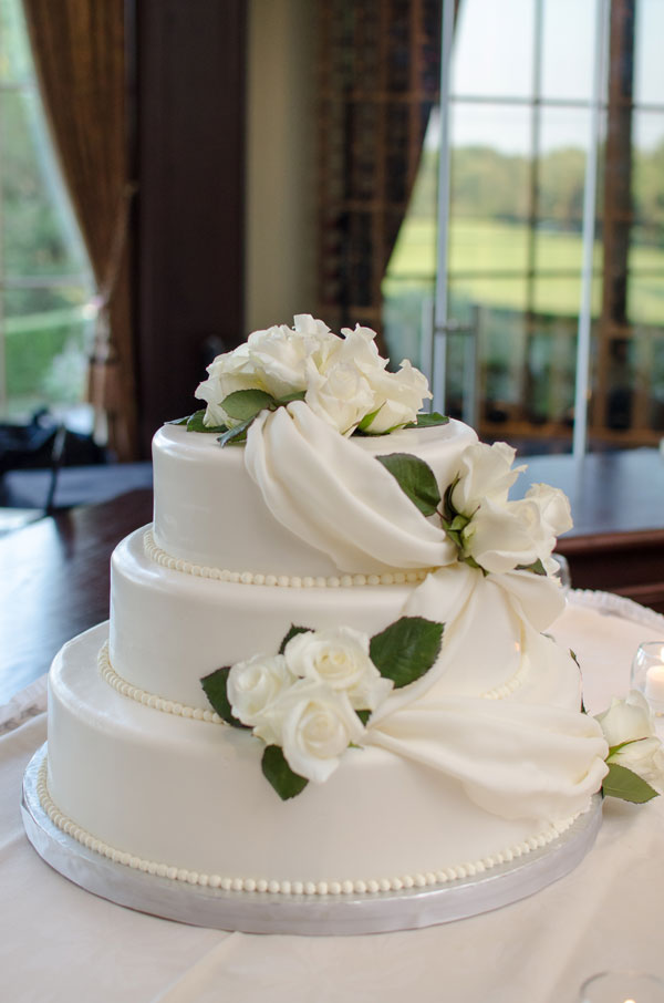 Three tier cake with piped pearls, white fondant draping detail and fresh white roses