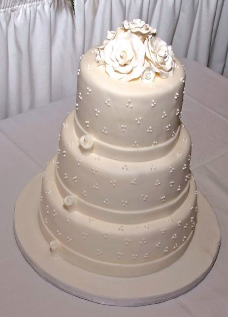 White three tier fondant cake with white fondant ribbon trim & fondant rose topper