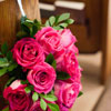 Bright pink rose bouquets tied to end of church pews with white ribbon