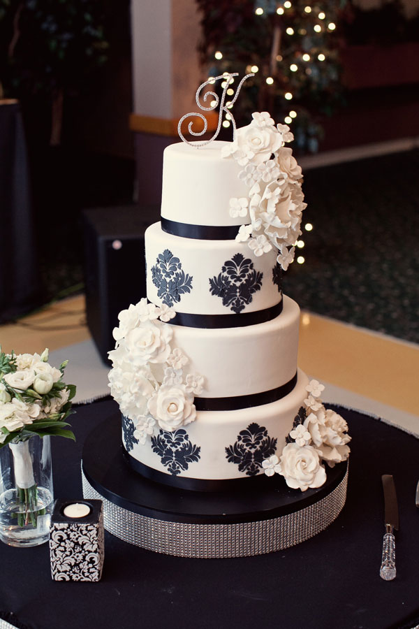 Black and white four tier cake with rhinestone trim at base, fondant decals and white flower accents.