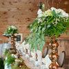 Reception tables lined with moss and tall copper flower stands