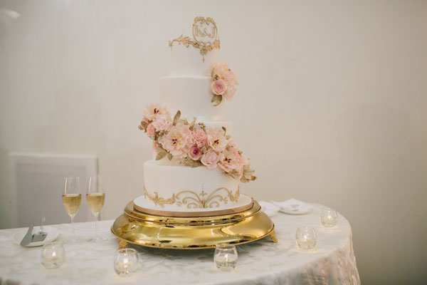 4 tier cake with cascading florals and gold lace applique trim