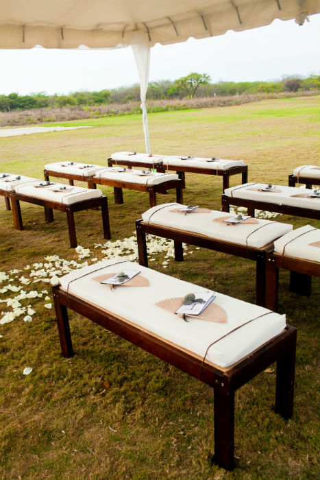 Rustic outdoor ceremony with vintage wood benches, and paper fan favours.