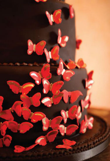 Romantic three tier dark brown fondant cake with petite red and gold fondant butterflies